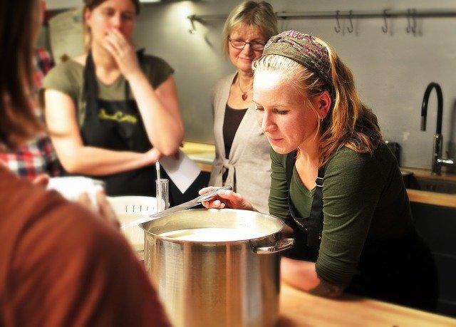 Photo d'un cours de cusine de 4personnes dont une dame blonde surveillant le contenu d'un fait-tout en inox