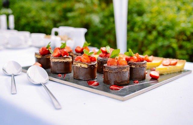 Photo d'un plateau de mignardises au chocolat et aux fraises posé sur une table nappée de blanc avec couverts de service