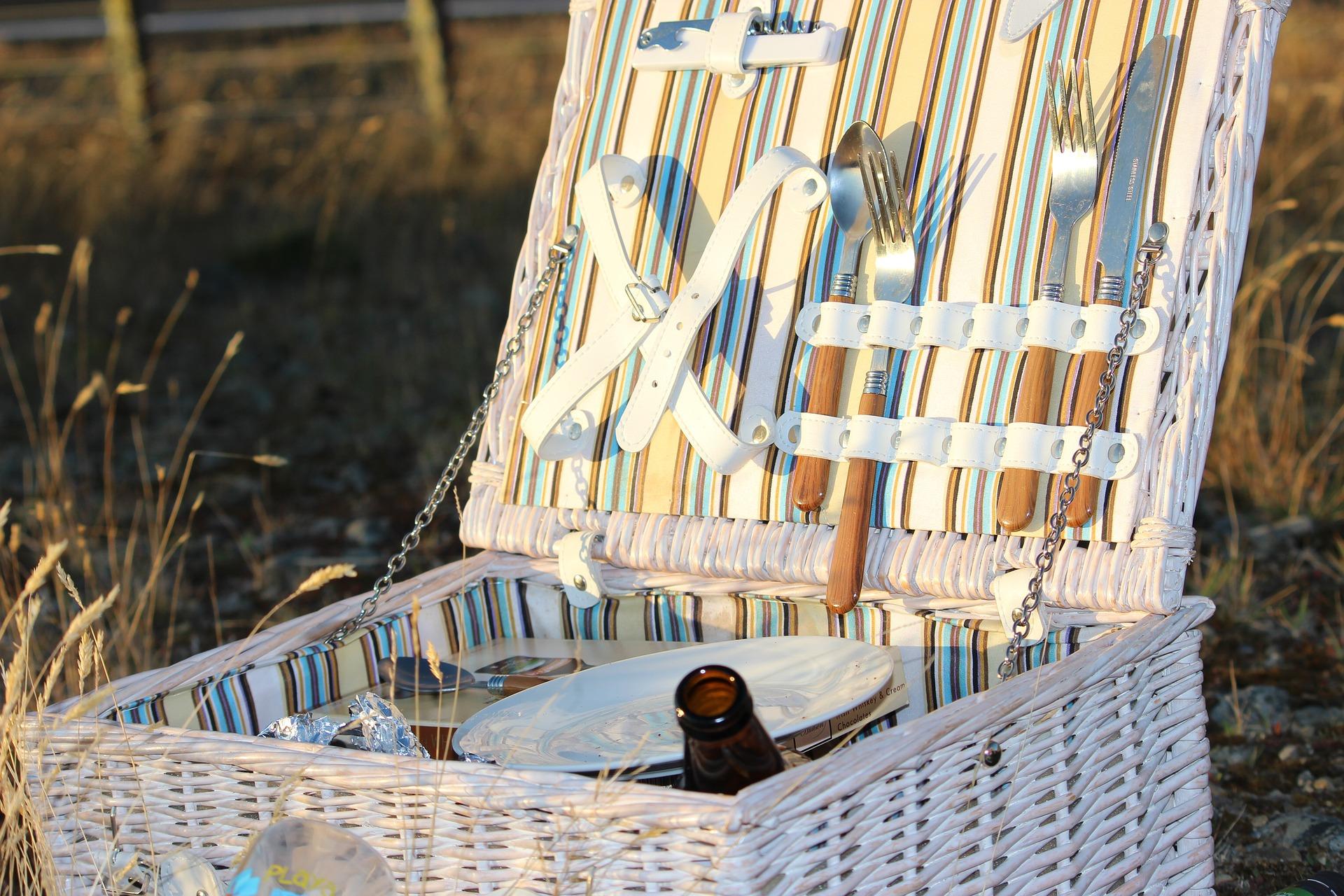 Photo d'un panier de pique-nique en osier blanc, intérieur rayé bleu ciel et blanc, avec nécessaire pour pique niquer, posé sur de l'herbe avec lumière du soleil couchant