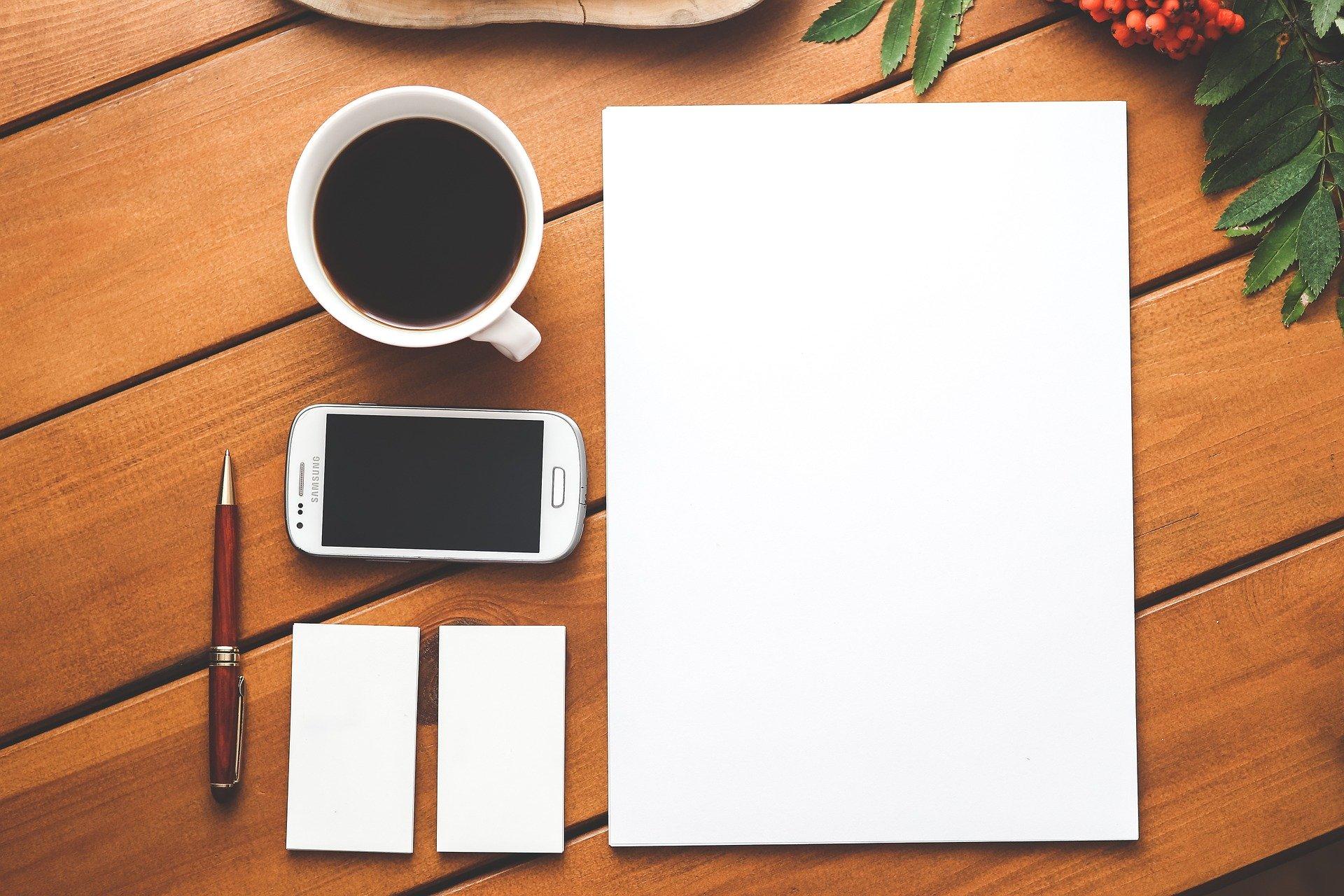 Photo où l'on peut voir de gauche à droite: tasse de café, téléphone portable, crayon de bois, post it blancs et bloc de feuilles A4 blanc sur fond en bois couleur chêne avec feuillage