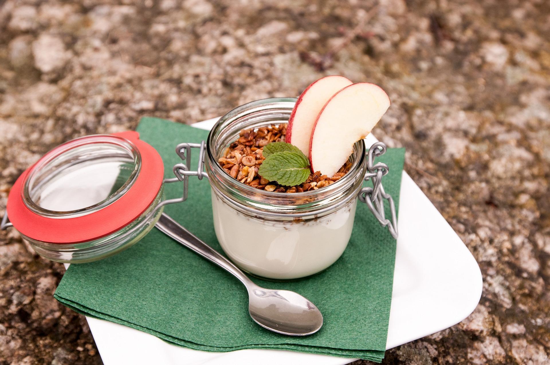 """Dessert: fromage blanc avec muesli et quartiers de pomme dans petit bocal style """"Le Parfait"""" posé dans une assiette en porcelaine blanche avec serviette vert sapin"""