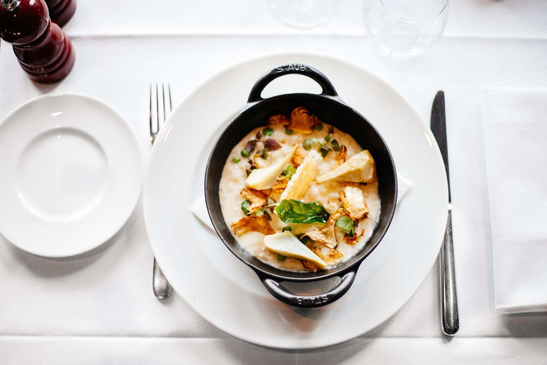 Plat végétarien cuisiné dans une petite cocotte noire posée sur une assiette en porcelaine blanche elle-même posée sur une table blanche